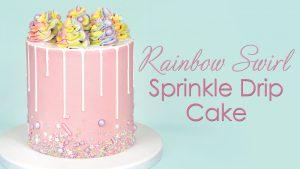pastel pink buttercream cake with white drip and rainbow swirls