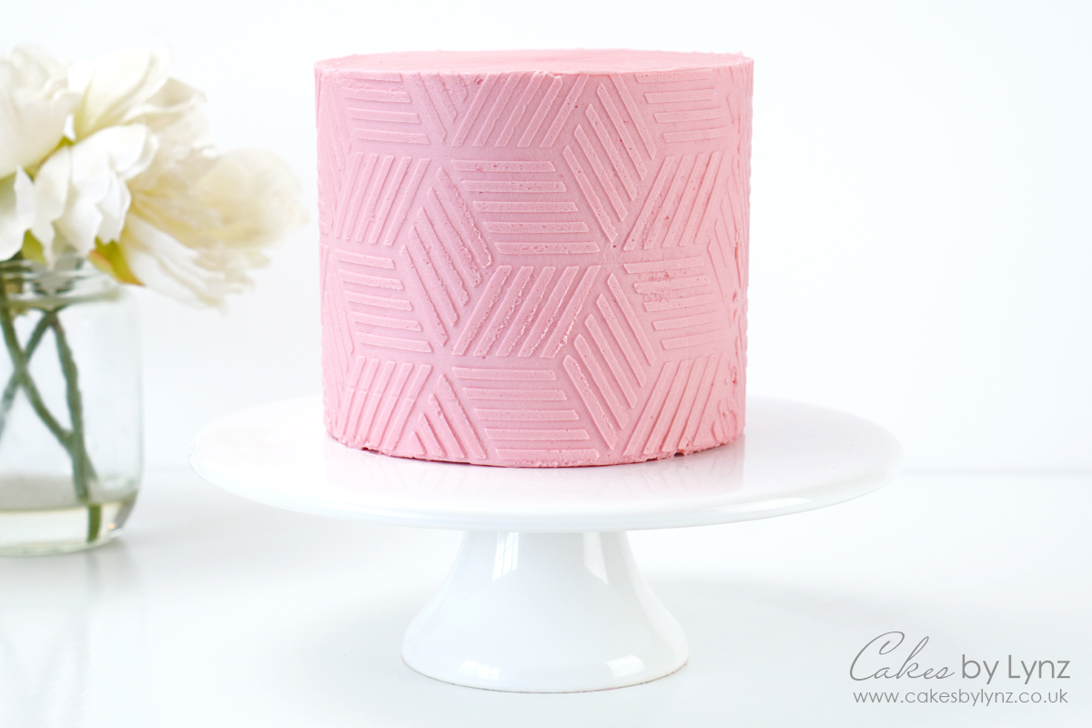 using a textures contour comb on a buttercream cake